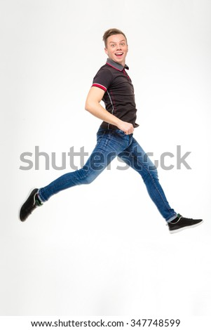 Full length photo of excited happy young man in black t-shirt and jeans jumping and running isolated on white background - stock photo