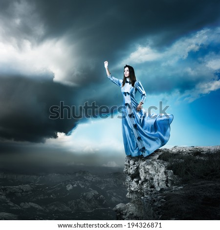 Full Length Photo of Fantasy Woman in Waving Blue Dress Reaching for the Light. Dramatic Moody Sky. HDR Cloudscape. - stock photo