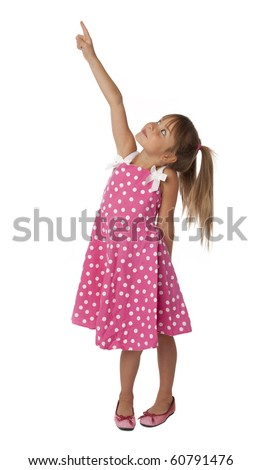 Full length photo of five year old girl in polka dot dress pointing upward. Isolated on white background. - stock photo