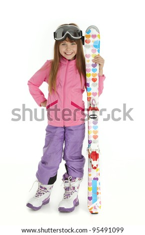 Full length photo of little girl dressed in ski wear holding colorful skis, standing on white background. - stock photo