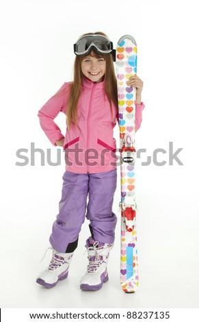Full length photo of little girl dressed in ski wear holding skis, standing on white background. - stock photo