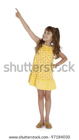 Full length photo of little wearing yellow summer dress pointing upward, on white background.