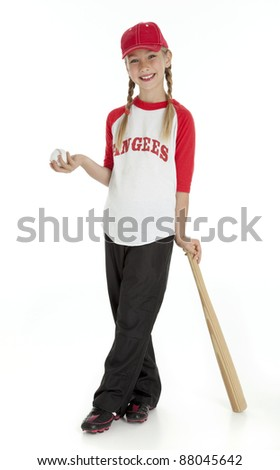 Full length photo of young girl dressed in baseball clothes, holding ball, leaning on bat. Isolated on white.