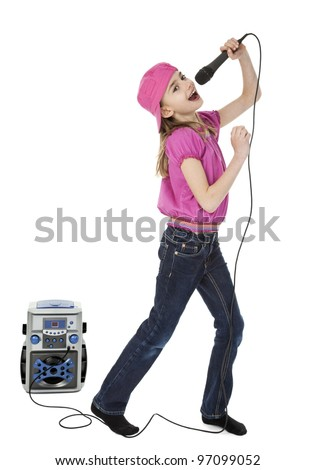 Full length photo of young girl singing into microphone with karaoke machine in background, isolated on white. - stock photo