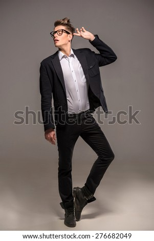 Full length photo of young handsome man dressed casual posing in the studio on dark background. Fashion portrait. - stock photo