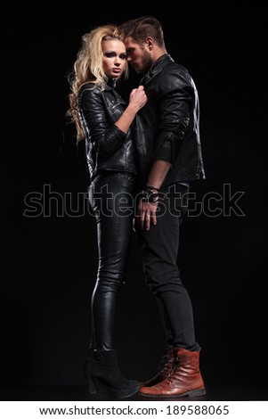 full length picture of a beautiful couple posing on a black studio background - stock photo