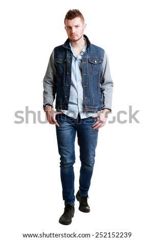 full length picture of a casual serious young man walking towards the camera  isolated over a white background - stock photo