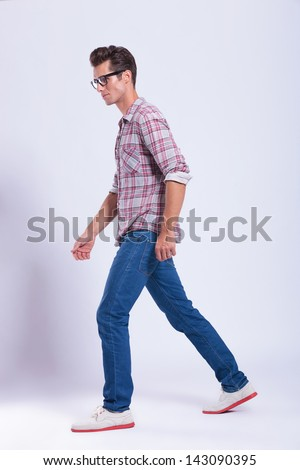 full length picture of a casual young man walking and looking away from the camera. on gray background - stock photo
