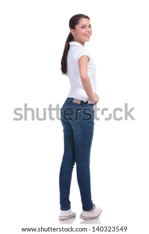full length picture of a casual young woman standing with her back to the camera and holding a hand on her hip while looking over the shoulder at the camera and smiling. isolated on white background - stock photo