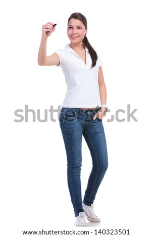 full length picture of a casual young woman writing on an imaginary screen and holding her other hand in the pocket. isolated on white background - stock photo