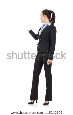 Full length picture of a confident business woman presenting something in the back and looking at it, isolated on a white background, a lot of copyspace