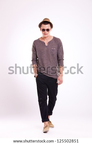 full length picture of a cool young man walking towards the camera with a hand in his pocket and looking forward with a serious look - stock photo