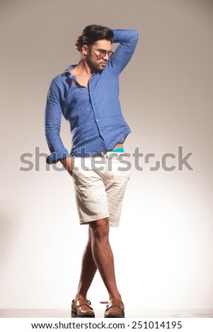 Full length picture of a handsome young fashion man standing on grey studio background. He is holding one hand in his pocket and the other one in his hair. - stock photo