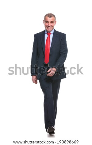 full length picture of a mid aged business man walking towards the camera and smiling. isolated on a white background - stock photo