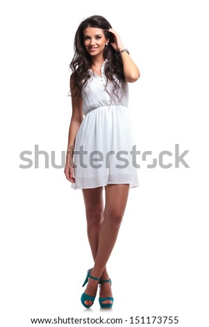 full length picture of a young beautiful woman passing her hand through her hair and smiling for the camera. isolated on a white background - stock photo
