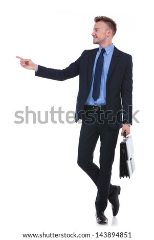 full length picture of a young business man holding a suitcase and pointing and looking to his side. on white background
