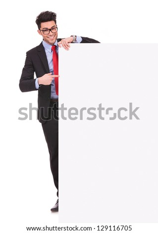 full length picture of a young business man holding an empty board and pointing to it while smiling to the camera on white background