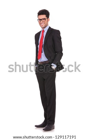 full length picture of a young business man holding his hands in his pockets while smiling to you, on white background - stock photo