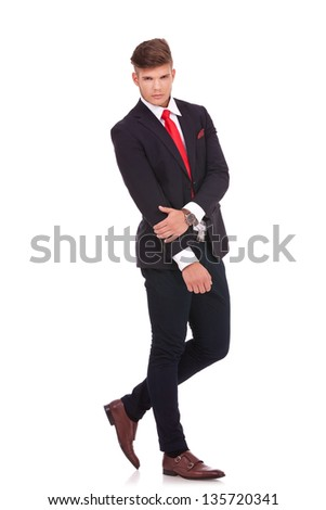 full length picture of a young business man posing with a serious expression on his figure while holding a hand with the other. isolated on white background - stock photo