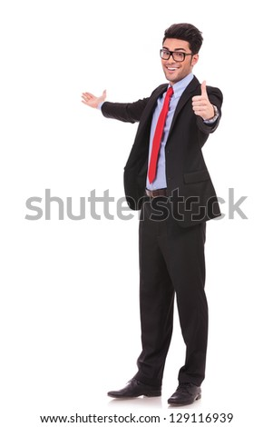 full length picture of a young business man presenting something in the back and showing thumbs up sign while smiling to the camera on white background - stock photo