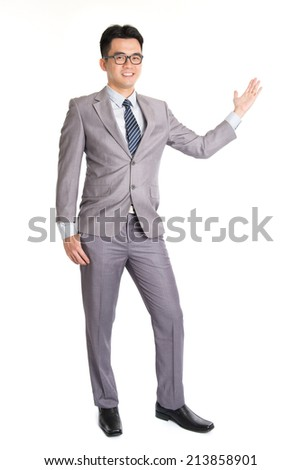 Full length picture of a young business man presenting something in the back with one hand in his pocket while looking at the camera with a smile on his face, isolated on white background. - stock photo
