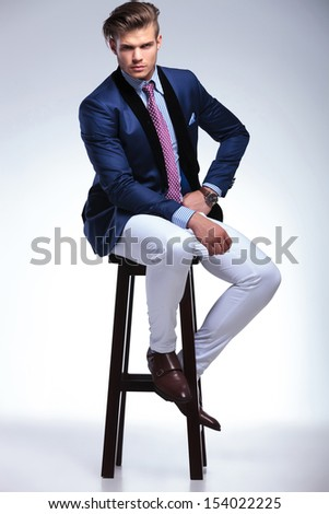 full length picture of a young business man sitting on a chair and looking at the camera with a hand on his hip and a serious expressiong. on a gray background - stock photo