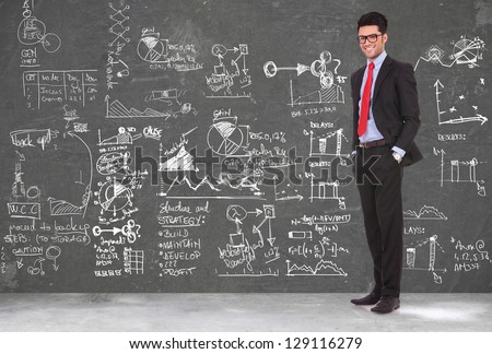 full length picture of a young business man standing with hands in pockets in front of a blackboard full of sketches and charts - stock photo