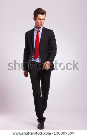 full length picture of a young business man walking forward and looking away from the camera, on gray background - stock photo