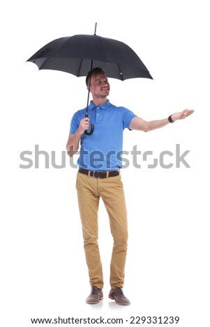 full length picture of a young casual man holding an umbrella and reaching a hand into the rain while looking at it. isolated on a white background - stock photo