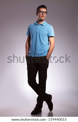 full length picture of a young casual man looking away from the camera while keeping his hands in his pockets. on white background - stock photo
