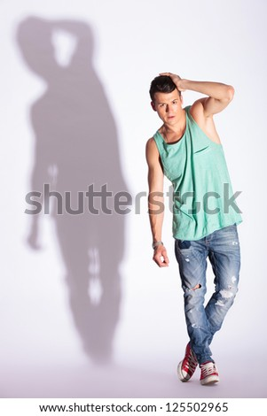 full length picture of a young casual man posing with his hand through his hair, on gray, with hard shadow - stock photo