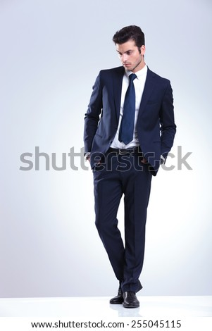 Full length picture of a young elegant business man looking down while holding both hands in his pockets. - stock photo