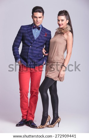 Full length picture of a young fashion couple standing on grey studio background.
