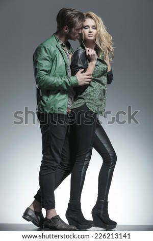 Full length picture of a young fashion man holding his girlfriend while she is fixing her hair. - stock photo