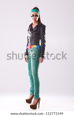 full length picture of a young woman in leather jacket and jeans looking at the camera - stock photo