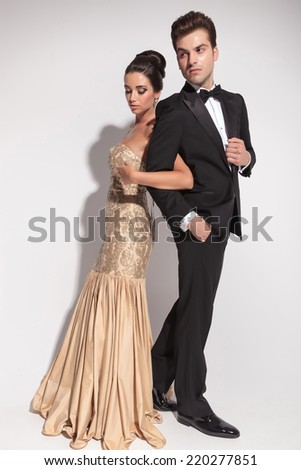 Full length picture of an elegant couple holding arms, looking away from the camera. - stock photo