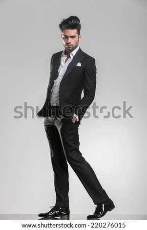 Full length picture of an elegant young man in tuxedo walking while holding his hand in pocket, looking at the camera. - stock photo