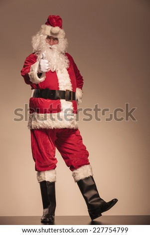 Full length picture of Santa Claus showing the thumbs up gesture. - stock photo