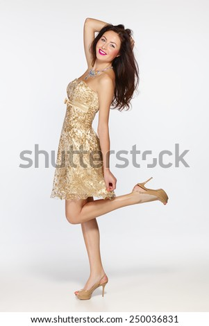 Full length playful beautiful woman in golden evening dress - stock photo