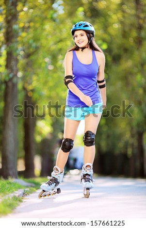 Full length portrait a young smiling female on rollers skating in a park - stock photo