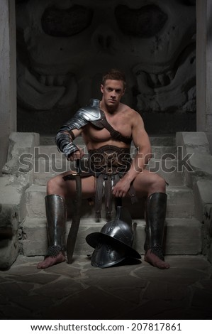 Full length portrait, gladiator in armour sitting on steps of ancient temple with helmet and sword, on dark background. Concept of masculine power, strength - stock photo