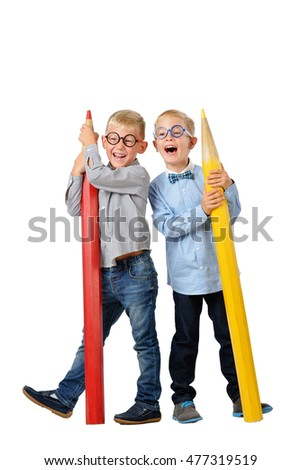 Full length portrait happy young boys in glasses and bowtie posing near huge colorful pencils. Educational concept. Isolated over white. School preschool