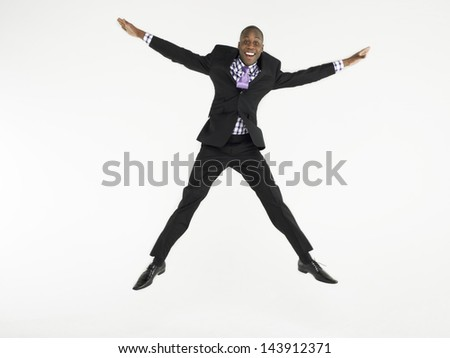 Full length portrait of a bald businessman jumping in star shape against white background - stock photo