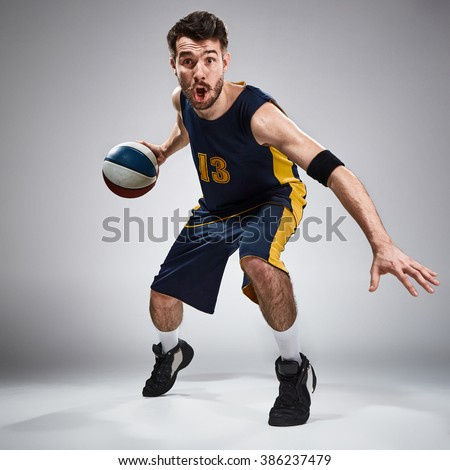 Full length portrait of a basketball player with a ball  against gray studio background - stock photo