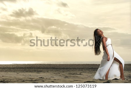 Full length portrait of a beautiful African American woman at the beach - stock photo