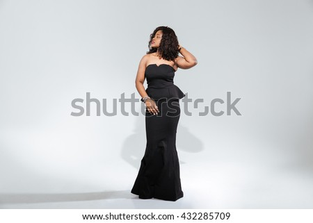 Full length portrait of a beautiful afro american woman in trendy dress posing isolated on a white background - stock photo