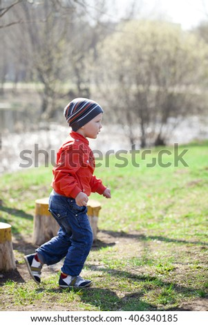 Full length portrait of a beautiful baby boy walking in spring park. Little boy in orange jaket and blue jeans, outdoors