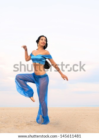 Full length portrait of a beautiful dancing girl in belly dance costume  - stock photo