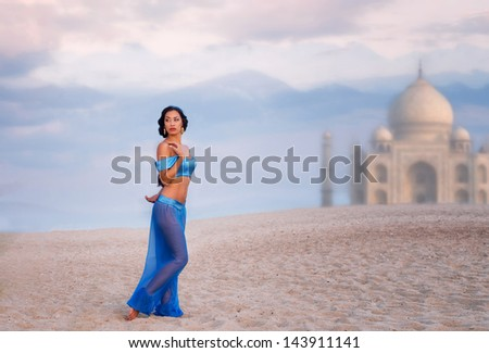 Full length portrait of a beautiful girl in belly dance costume with an image of eastern palace in the distance - stock photo
