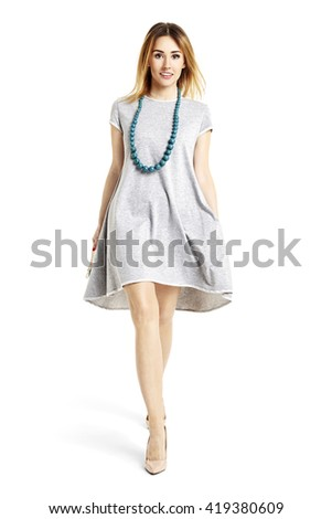 Full length portrait of a beautiful girl walking and looking at you.  - stock photo